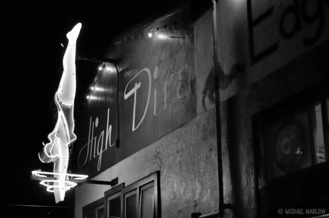 "neon sign of diving woman entering water for club called ""High Dive"" in black and white"