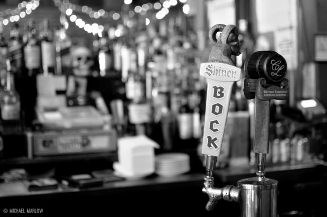 tap handles with blurred background of liquor bottles and cash register and human skull