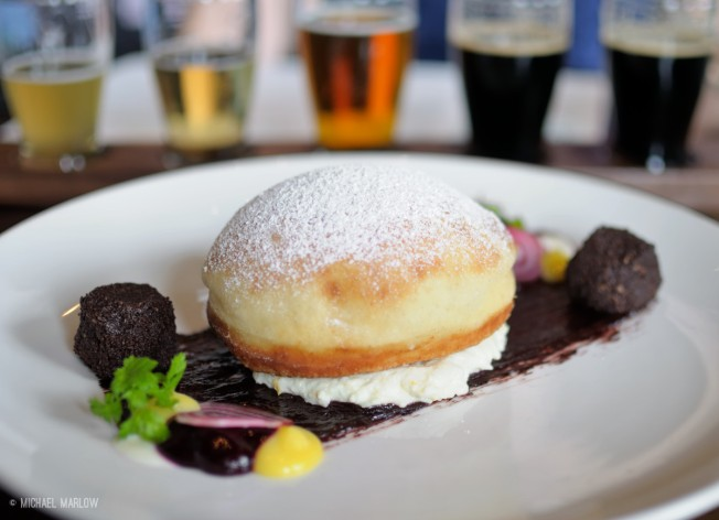 Doughnut covered with powdered sugar with light to dark flight of beers in background