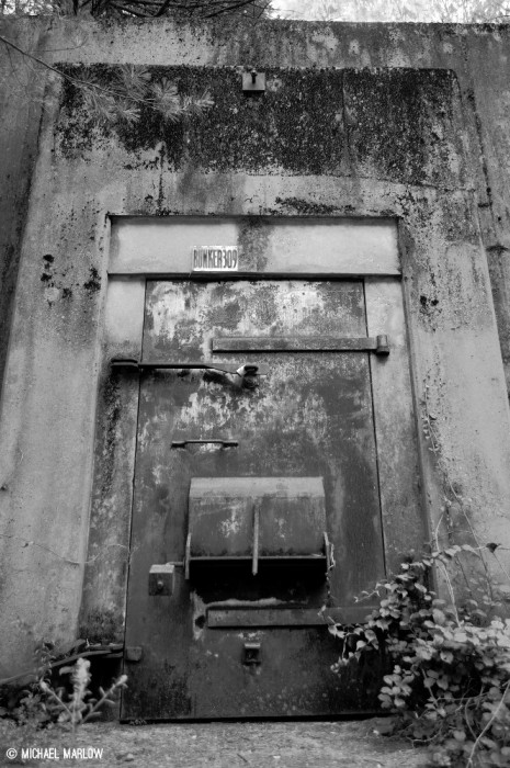 a weather worn cement bunker door with rusted locking bars firmly shut