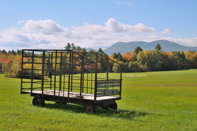 bale wagon in an open field before the changing foliage and mountains
