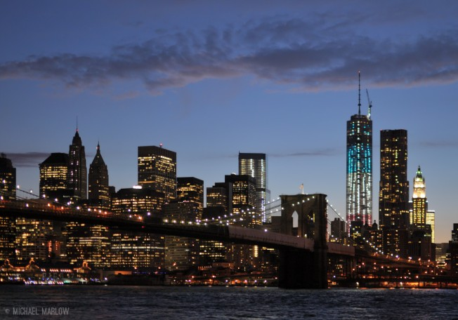 skyscrapers with lit up windows and american flag on top of brooklyn bridge in front