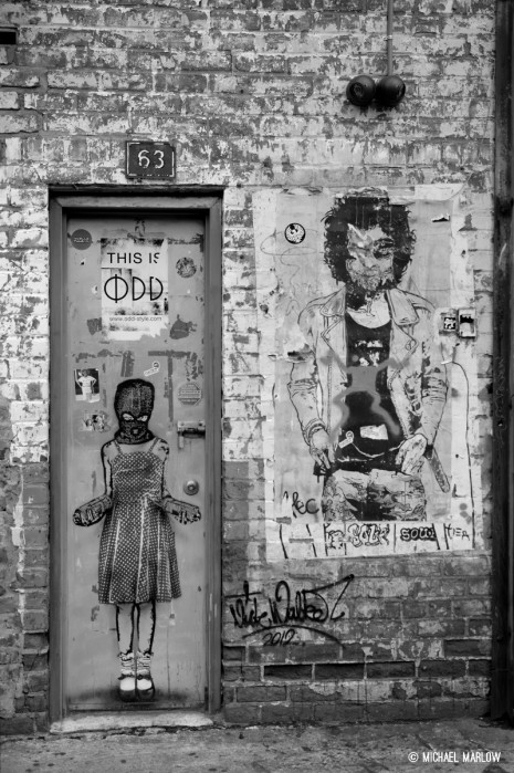 graffiti on door and brick wall of building including hooded red-dress girl