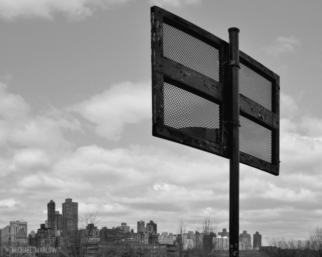 the backside of wooden frame and screen backboard with skyline in background