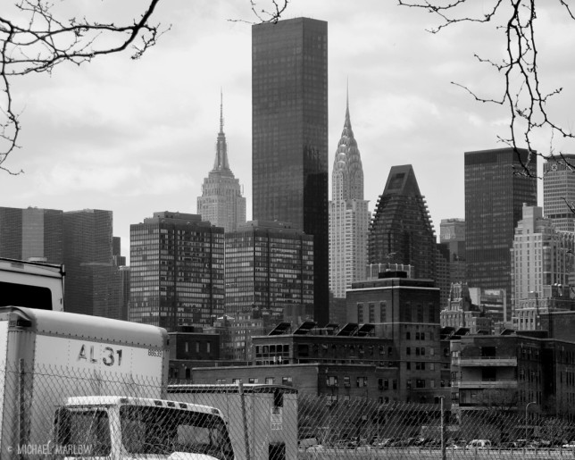 skyscrapers in background with partial view of box truck and tree branches in foreground