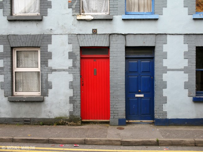 red and blue doors surrounded by windows right on sidewalk with edge of street showing
