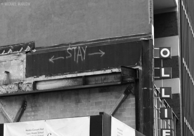 "rusted beams exposed with ""STAY"" and arrows spray painted abutting building with vertical OLLIE sign"