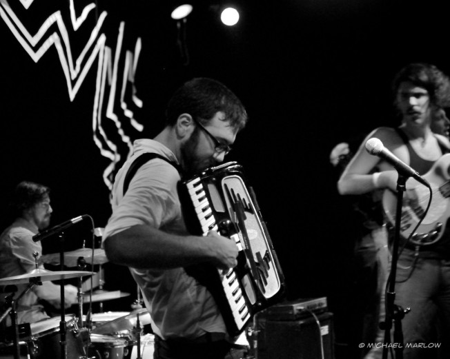 man playing accordion with drummer and guitarist in the background