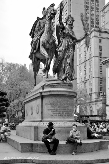 a boy and a man eating ice cream cones while sitting at base of large statue