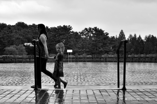 A woman and child walk past the second railing