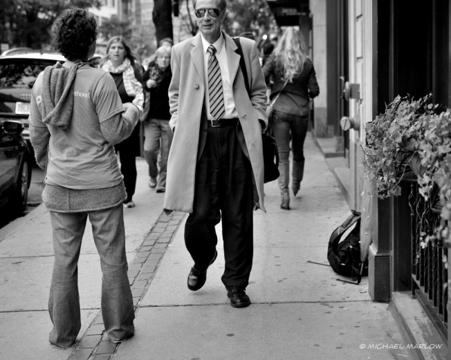 A man in a suit withsunglasses approaches a solicitor on the sidewalk