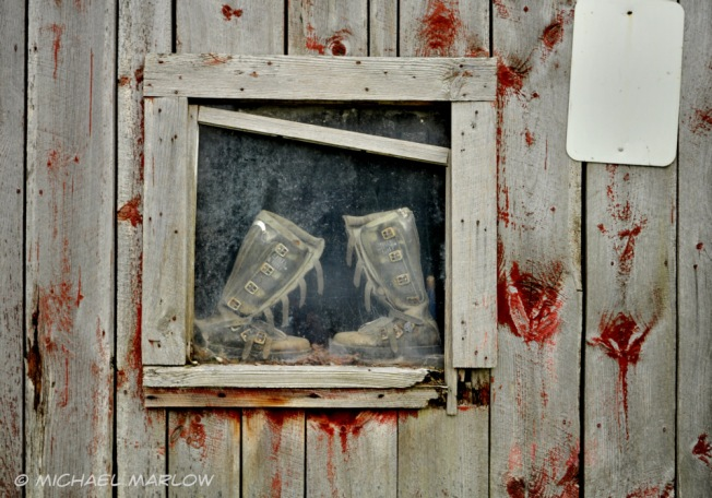 old boots in a window of a wall of weatherbeaten boards with knots painted red