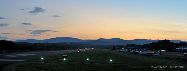 sun set behind mountains in front of an airport run with biplanes lined up at left